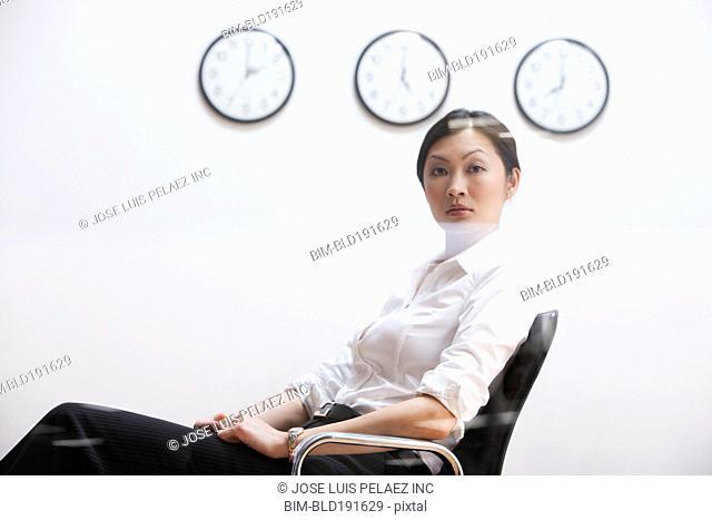 Serious Chinese businesswoman sitting under clocks