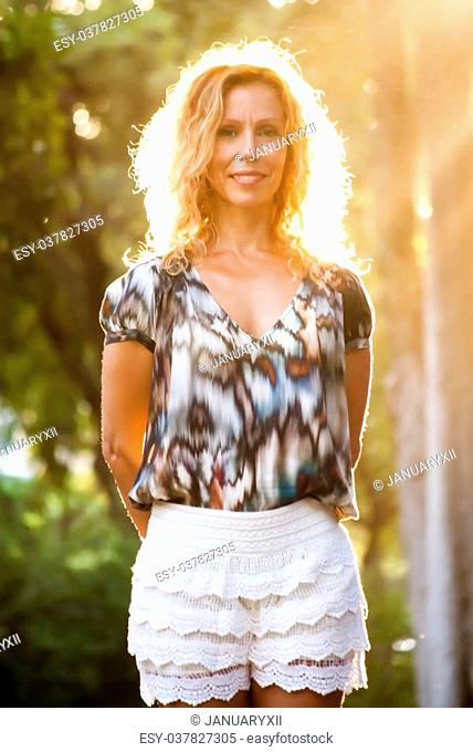Back Light Portrait of middle aged pretty woman In The Park