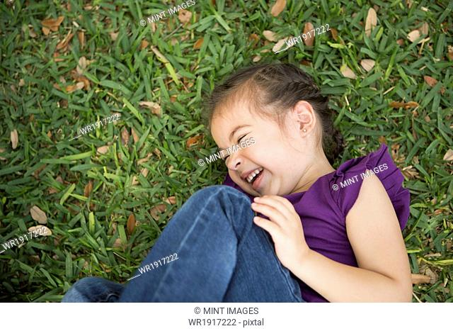 A girl lying on her side with her knees drawn up laughing