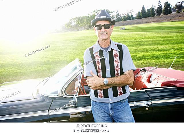 Mixed race man smiling near classic convertible
