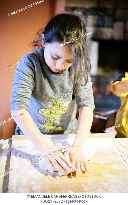 Child kneads the flour to make a cake