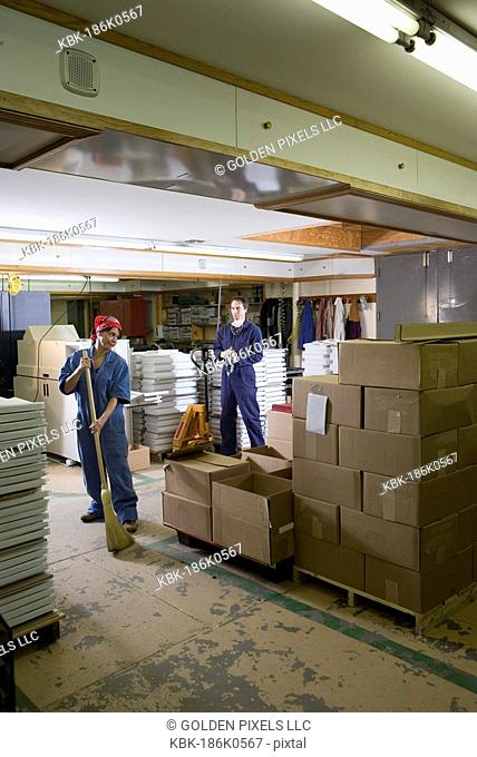 Portrait of a man and a woman in coveralls working in a warehouse