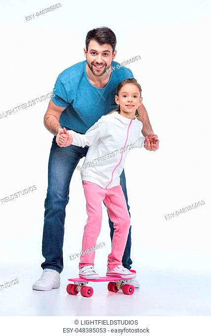 smiling father helping daughter to ride skateboard on white