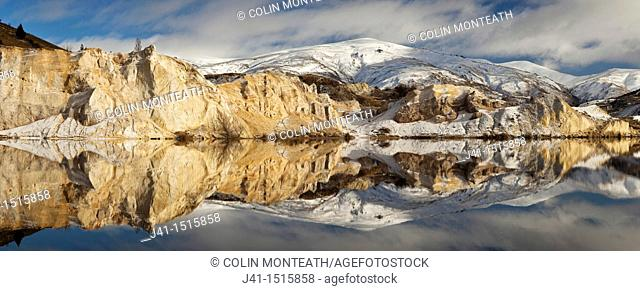 Blue lake reflection panorama after winter snow fall, St Bathans historic gold fields township, Central Otago, South Island, New Zealand