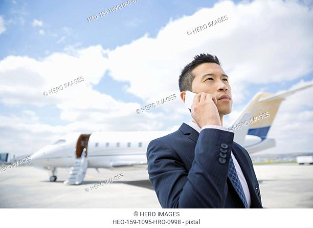 Businessman talking on cell phone on tarmac