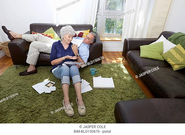 Older couple looking at photographs in living room