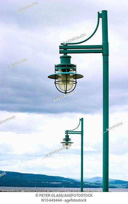 Streetlights beneath a cloudy sky