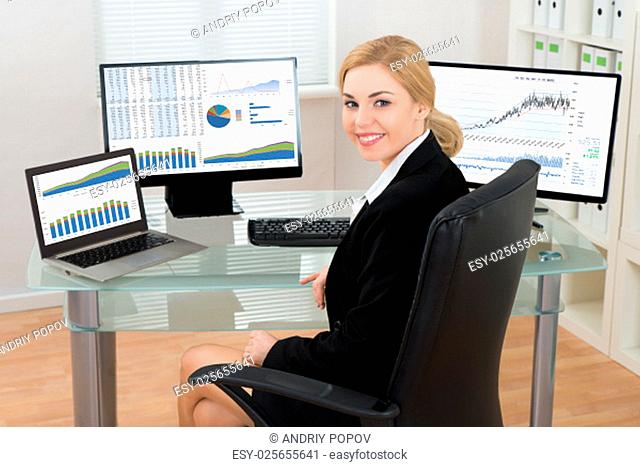 Happy Businesswoman On Office Chair With Computers Display Showing Graphs At Desk