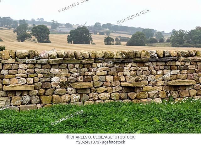 UK, England, Yorkshire. Stone Wall, Farmland in Background