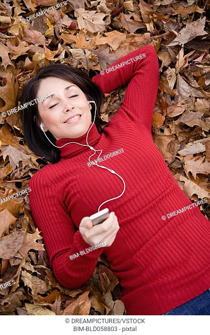 Hispanic woman listening to mp3 player in autumn leaves