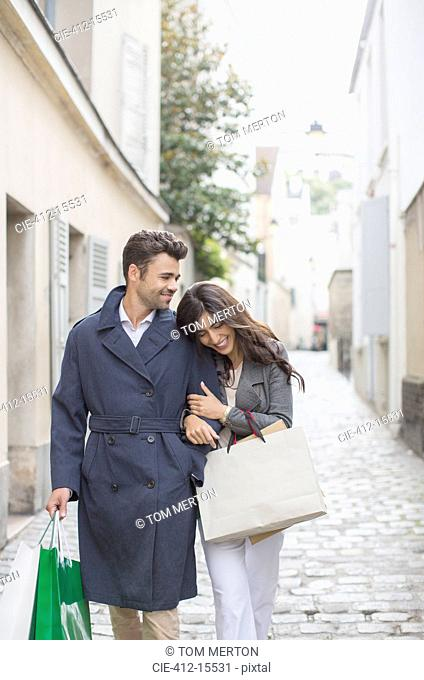 Couple carrying shopping bags on cobblestone street near Sacre Coeur Basilica, Paris, France