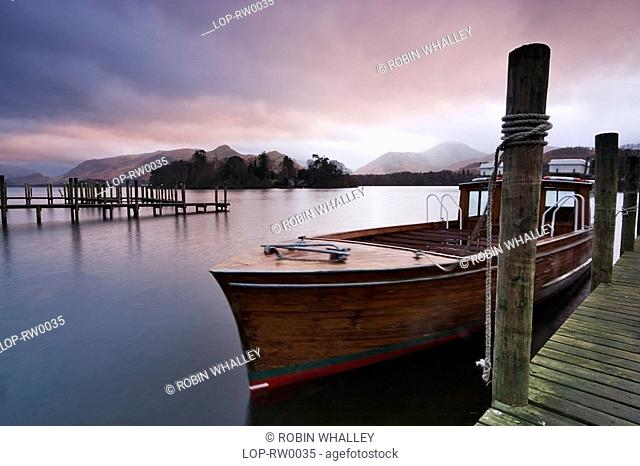 England, Cumbria, Derwent Water, Boats tied up on the landing stage at Derwent Water. Watched over by the fells of Derwent, and Castlerigg