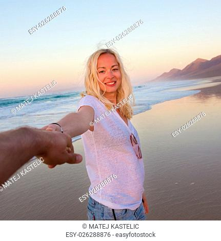 Young romantic couple, holding hands, having fun on perfect deserted beach at sunset. Shot from boyfrieds perspective. Guy looking at her beautiful carefree...