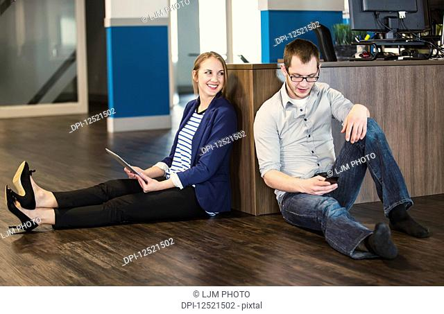 Two young millennial professionals taking a break and sitting on the floor of their workplace using technology; Sherwood Park, Alberta, Canada