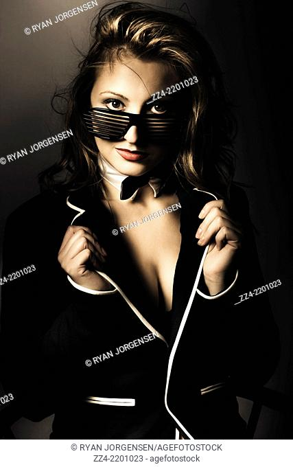 Fashion photo of beauty woman posing in elegant dress suit jacket and bowtie on dark background. Formal evening wear