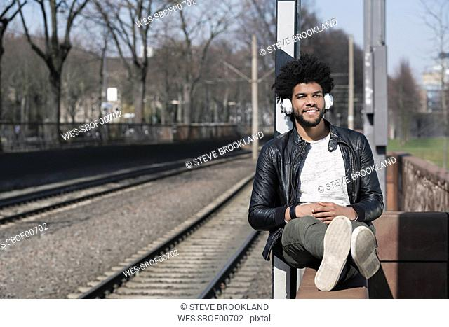 Smiling man sitting on wall listening to music next to train rails