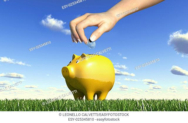 Woman hand inserting a coin into a yellow ceramic piggy bank placed on a green grass meadow, viewed from a side close up, with blue sky and fluffy clouds