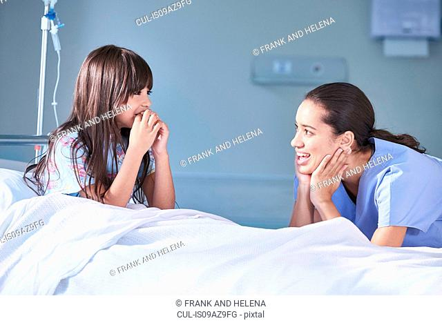 Girl patient talking to female nurse in hospital children's ward