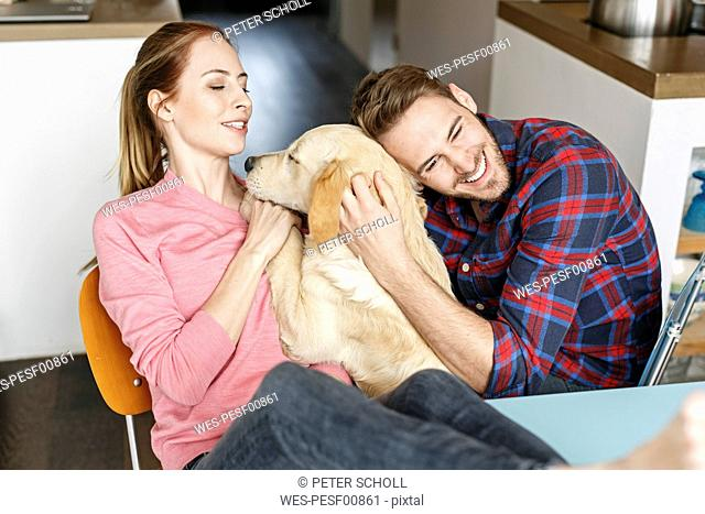 Happy young couple cuddling with dog at home