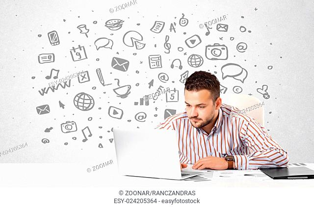 Young businessman with all kind of hand-drawn media icons in background