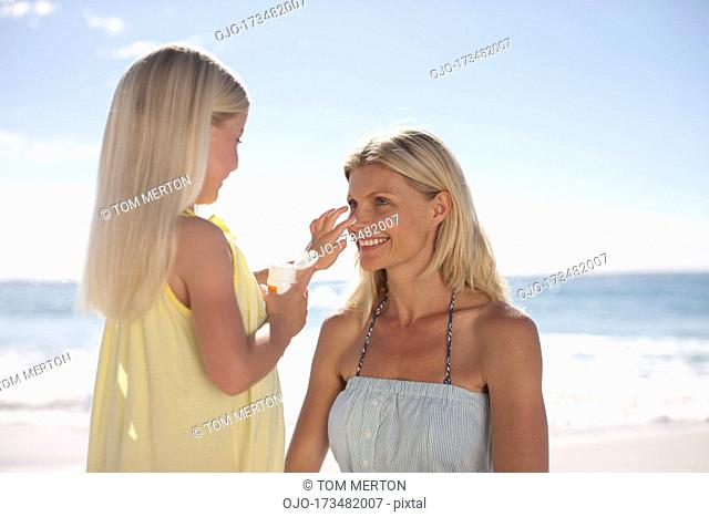 Girl applying sunscreen to mother's nose on beach
