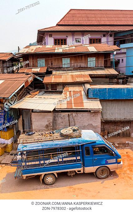 Buildings and van on the street leading down to the river Nam Ou. Muang Khua, Laos, Southeast Asia
