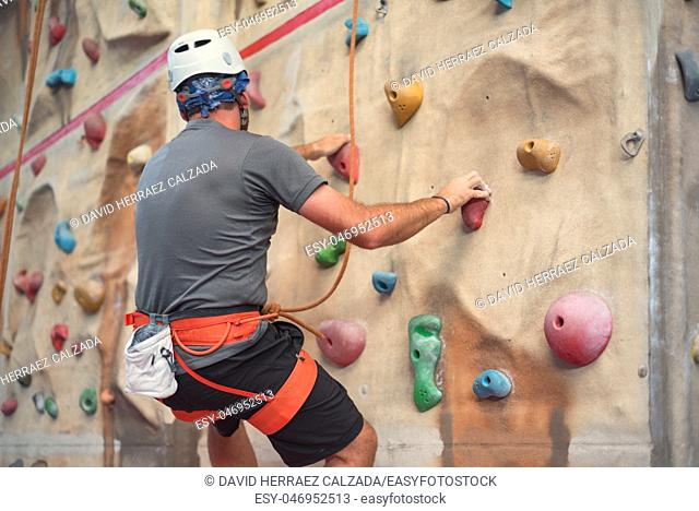 Young man practicing rock climbing on artificial wall indoors