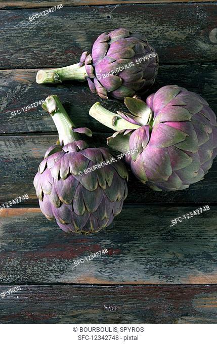 Purple Tunisian artichokes on a wooden board