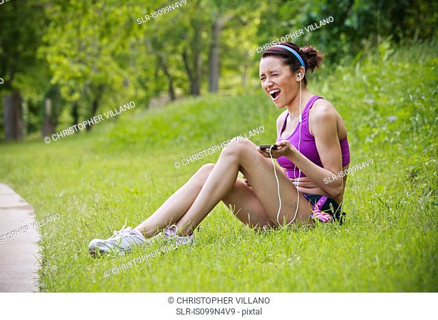 Injured young woman listening to mp3 player