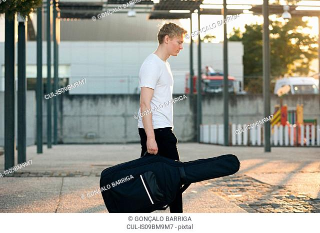 Young musician carrying guitar in case