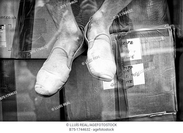 closeup of feet, unrecognizable person sitting on cardboard boxes