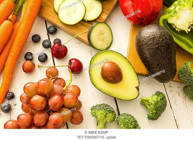 Avocado and red grapes surrounded by fruits and vegetables