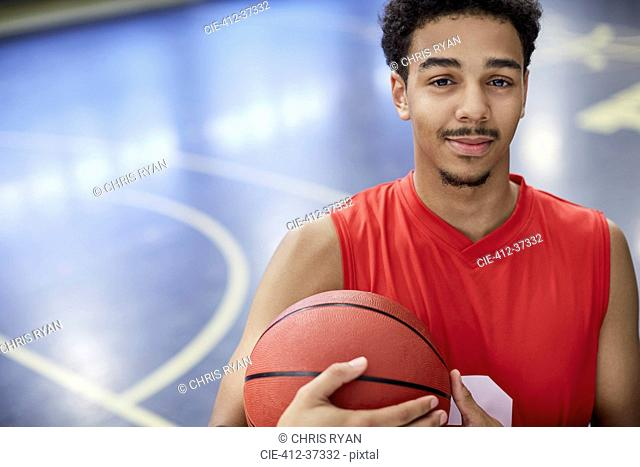 Portrait confident young male basketball player holding basketball on court
