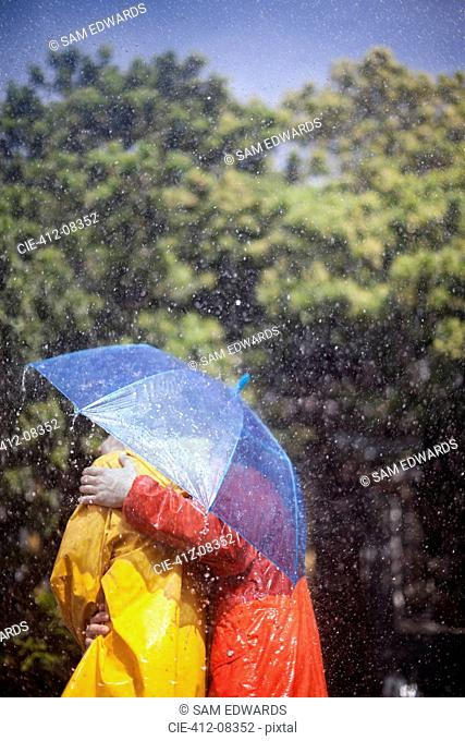 Couple hugging under umbrella in rain