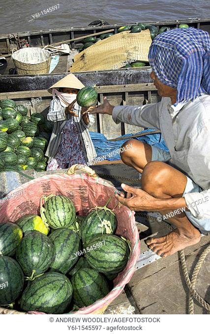 Man passing melons to woman in conical hat Cai Ran floating market near Can Tho Vietnam