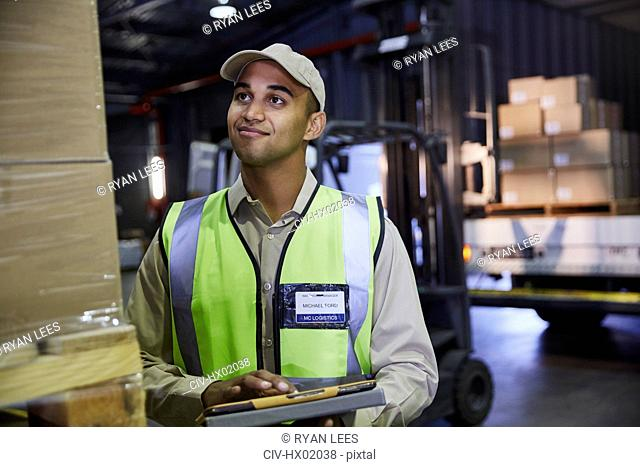 Worker with clipboard checking boxes in distribution warehouse