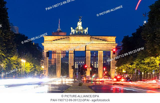 12 July 2019, Brandenburg, Berlin: Passing cars leave light tracks on the Straße des 17. Juni. In the background you can see the Brandenburg Gate (photo with...