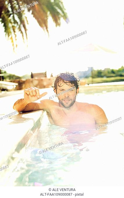 Man relaxing in pool, portrait