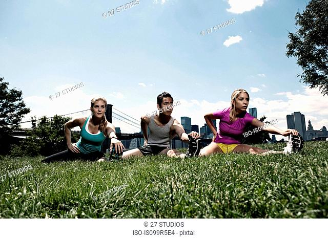 Three people stretching in park