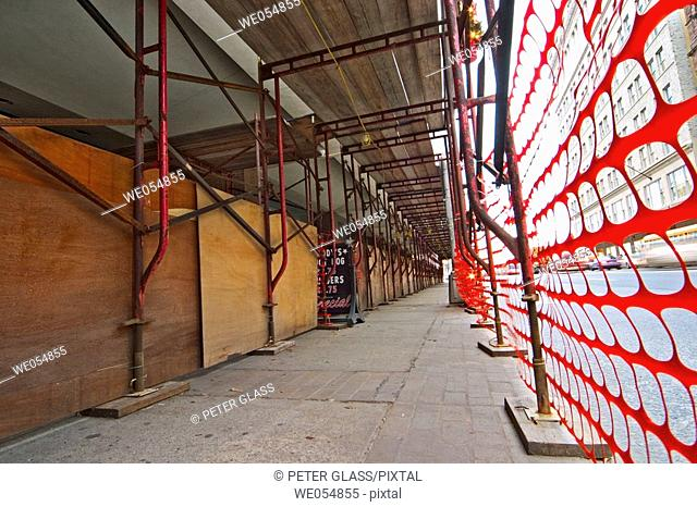 Scaffolding, sheets of plywood, and a protective net on a city street