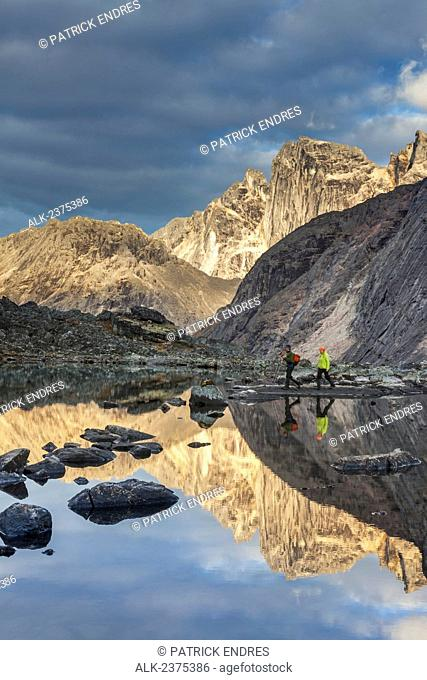 Hikers view Camel peak reflecting in a mountain lake in the Arrigetch Peaks, Gates of the Arctic National Park, Alaska