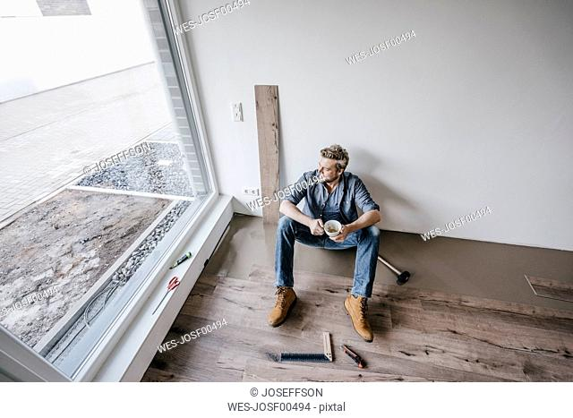 Mature man fitting flooring in new home, drinking coffee and taking a break