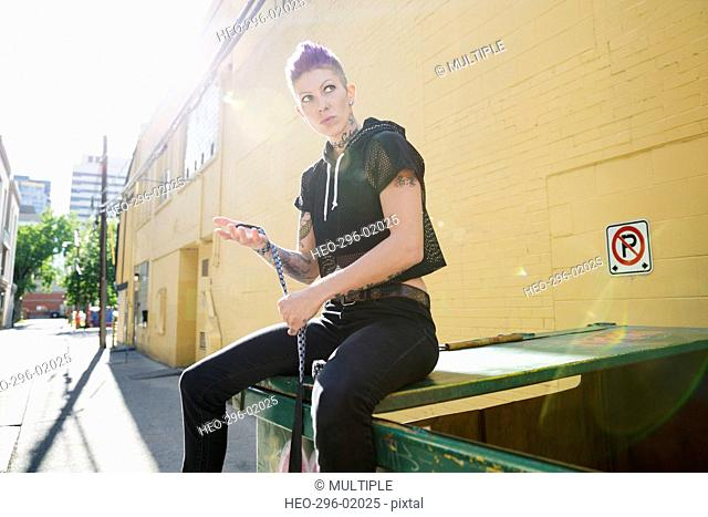 Cool young woman sitting on top of dumpster in sunny urban alley