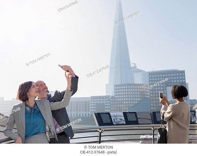 Business couple taking selfie with camera phone, London, UK