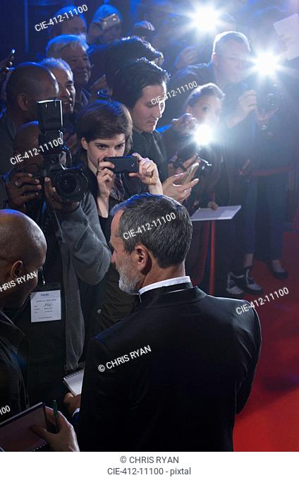 Well dressed male celebrity signing autographs at red carpet event