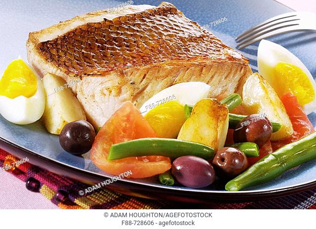 Grilled fish with hard boiled eggs and vegetables and olives, food