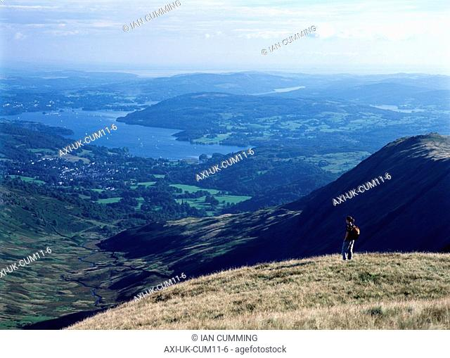 Walker admiring view on the descent from Rydal Head looking towards Ambelside and Lake Windermere