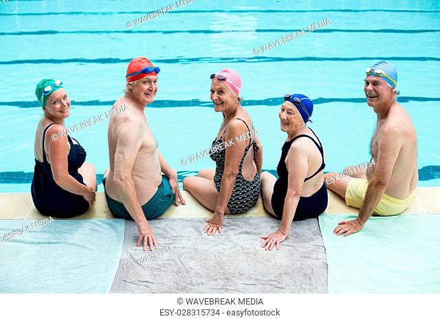 Cheerful senior swimmers sitting at poolside