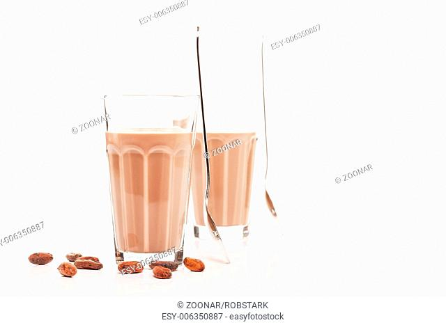 two glasses with chocolate milk and chocolate bean
