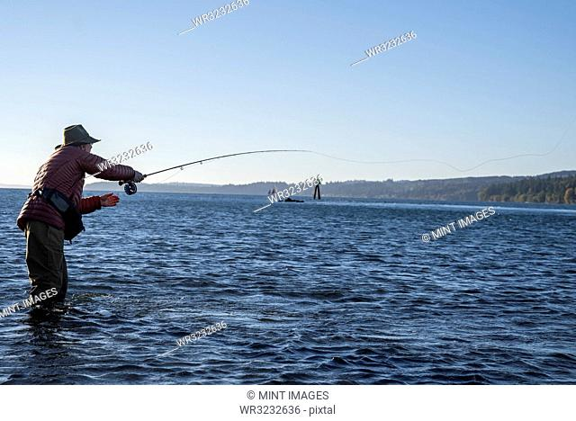 A Caucasian male fly fisherman casts for searun coastal cutthroat trout and salmon in salt water off Indian Island in northwest Washington State, USA